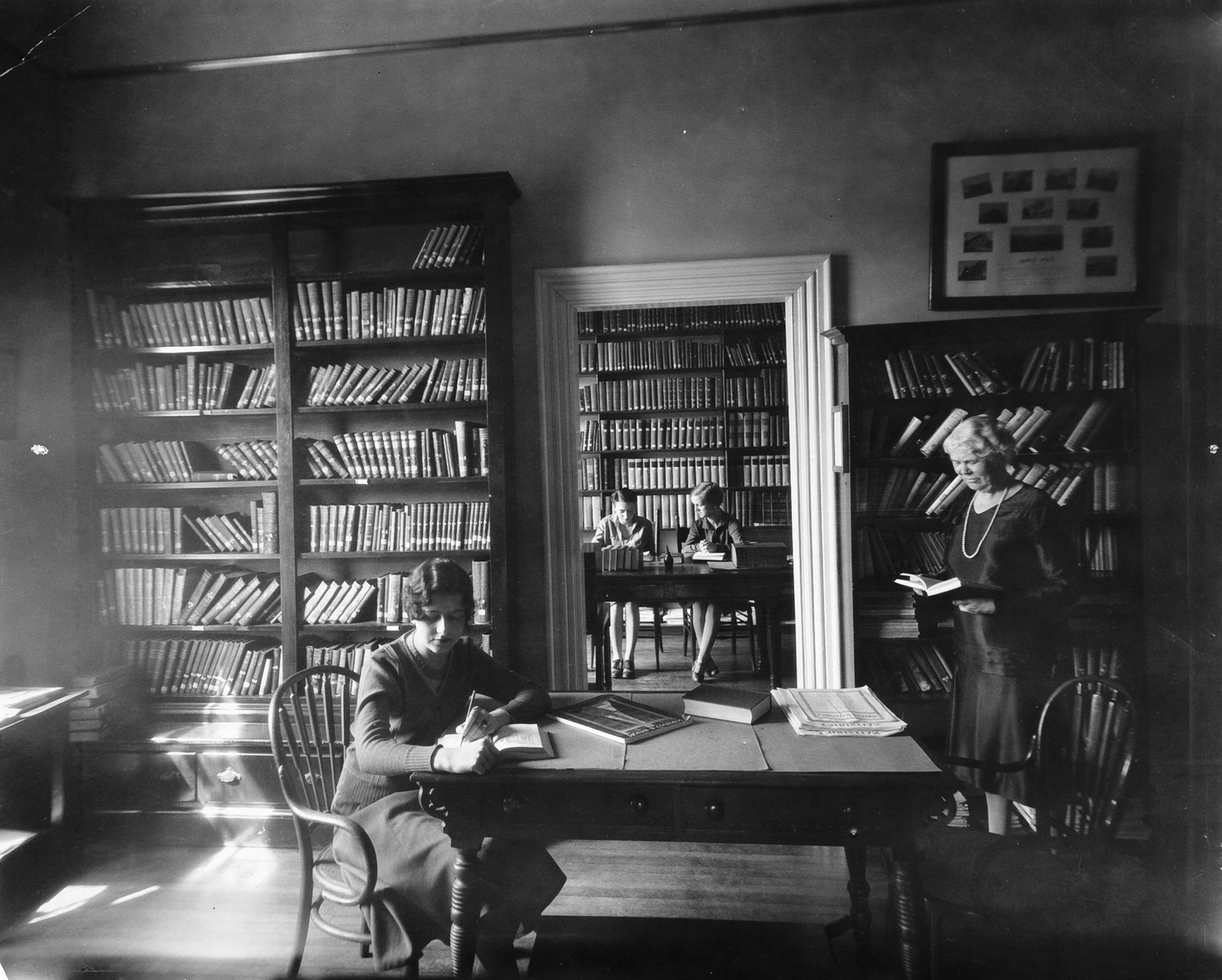 Black and white historic photograph of women studying in a library