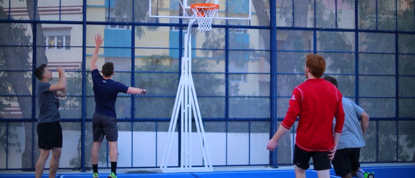 学生们 play basketball on the basketball and volleyball court at U N E Tangier