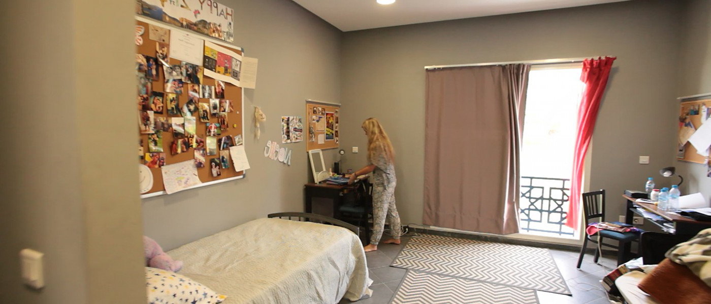 A student near the balcony doors in her modern dorm room within the U N E Tangier residences